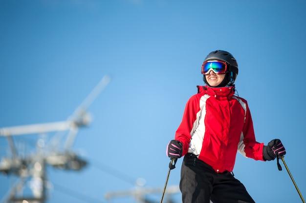 Frau, die mit skis auf die gebirgsoberseite steht