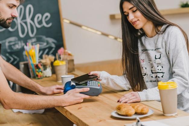 Frau, die mit smartphone im café zahlt
