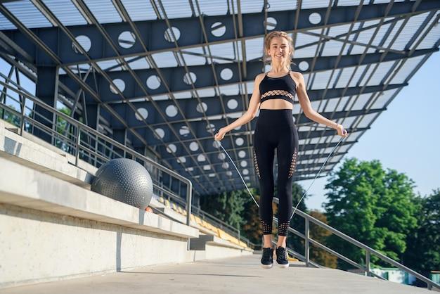 Frau, die mit springseil am stadion springt. aktive fitnessfrau, die übungen im freien macht. fitness-konzept. gesunder lebensstil.