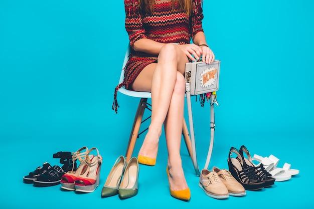 Frau, die mit stilvoller schuhsommermode und -tasche, lange beine, einkaufen aufwirft