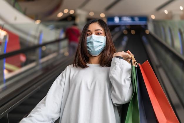 Frau, die mit tasche im einkaufszentrum einkauft und medizinische maske zur verhinderung von coronavirus trägt
