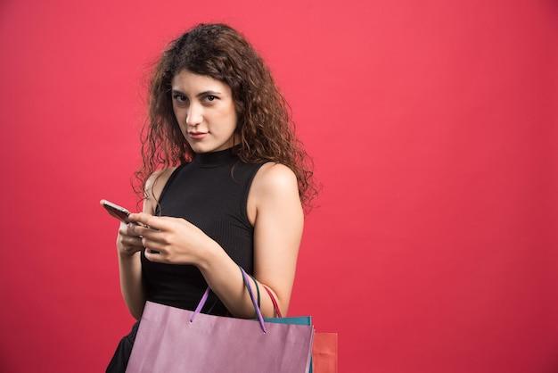 Frau, die mit taschen voller neuer kleidung und telefon auf rot lächelt