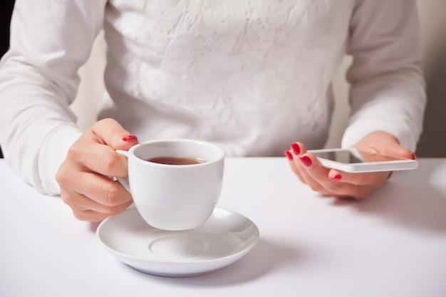 Frau, die mit tasse kaffee sitzt und handy verwendet