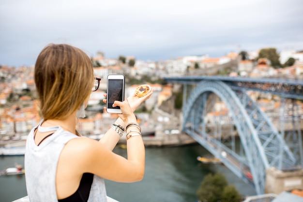 Frau, die mit telefon traditionelle portugiesische dessertpastell de nata auf dem stadtbildhintergrund in porto fotografiert?