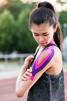 Frau, die mit therapeutischem band auf aschenbahn des sports sta aufnimmt