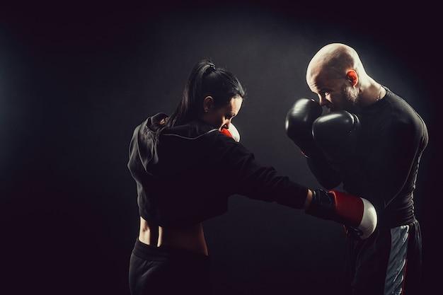 Frau, die mit trainer an der box- und selbstverteidigungsstunde trainiert