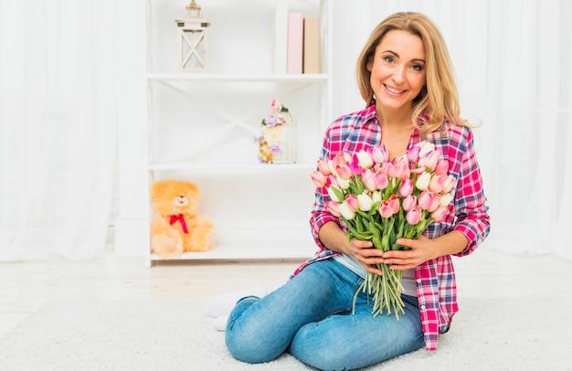 Frau, die mit tulpenblumen auf boden sitzt