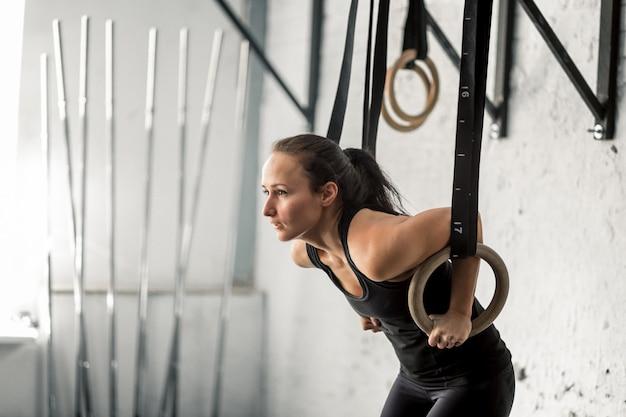 Frau, die mit turnringen am cross-fit-fitnessstudio trainiert