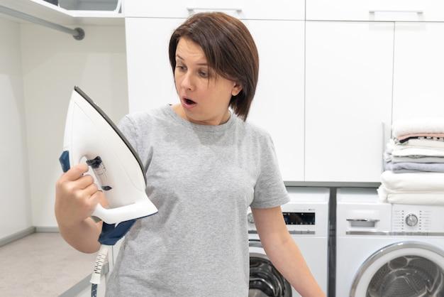 Frau, die mit überraschung unten des defekten eisens in der waschküche mit waschmaschine schaut