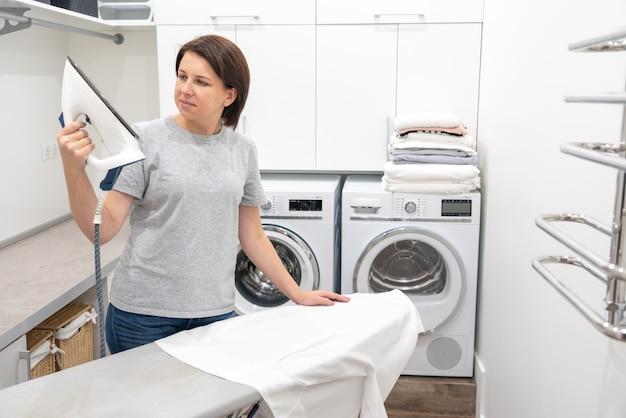 Frau, die mit überraschung unten eisen in der waschküche mit waschmaschine betrachtet