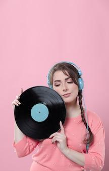 Frau, die mit vinylaufzeichnung und kopfhörern aufwirft