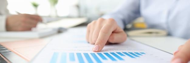 Frau, die mit zeigefinger wachstum des gewinns im finanzprognosekonzept der diagrammnahaufnahme zeigt