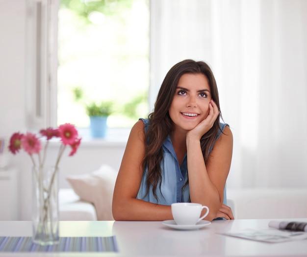 Frau, die mit zeitung und kaffee entspannt