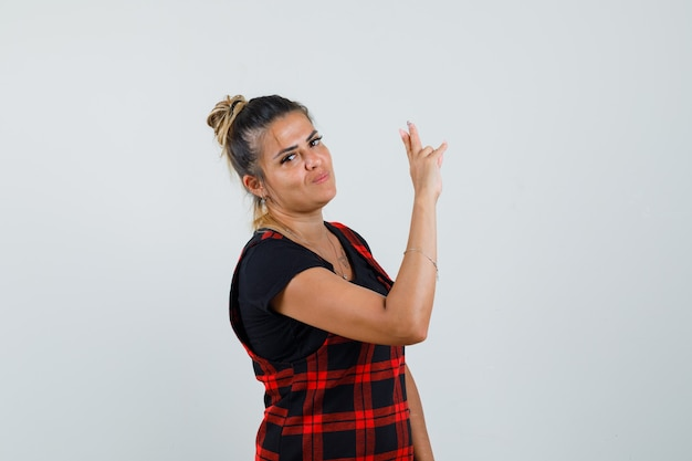 Frau, die mit zwei fingern im trägerkleid gestikuliert und selbstbewusst aussieht. vorderansicht.