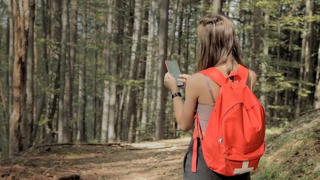 Frau, die mitten im wald steht, die navigations-app auf dem smartphone verwendet, der route mit hilfe der karte folgt, den gerätebildschirm betrachtet, die smartphone-navigation verwendet, während sie sich im wald verliert.