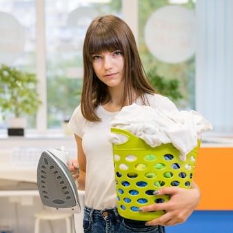 Frau, die mittleren schuss des wäschekorbes hält