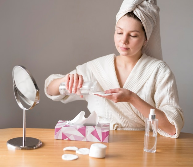 Frau, die mizellenwasser verwendet, um zu reinigen