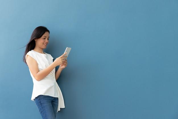 Frau, die mobile oder smartphone mit kopienraum auf blauer wand verwendet
