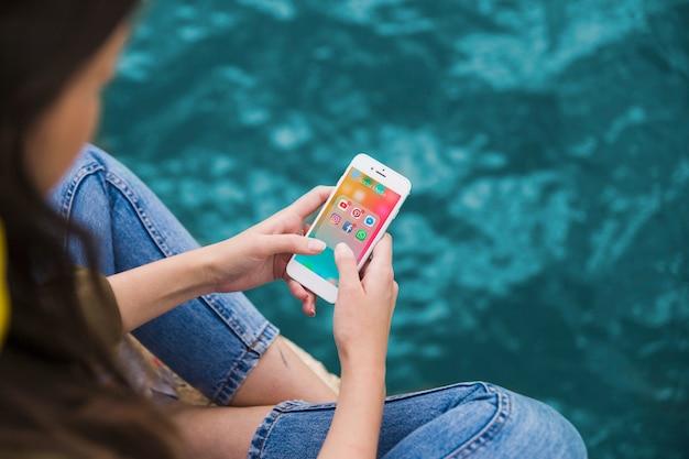 Frau, die mobiltelefon mit social media-benachrichtigungen auf schirm verwendet