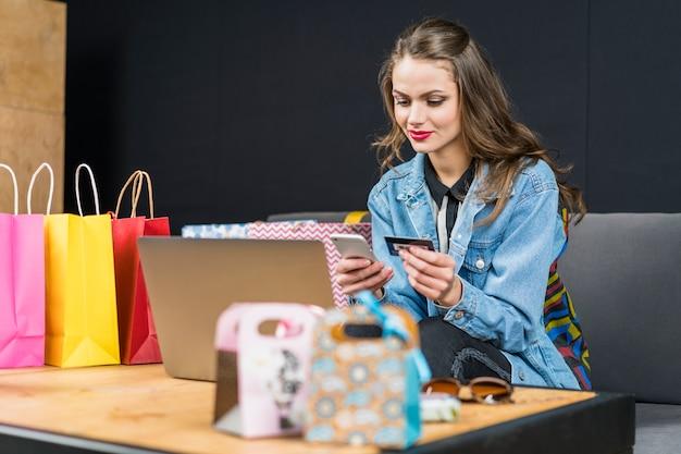 Frau, die mobiltelefon und chipkarte für online zu hause kaufen verwendet