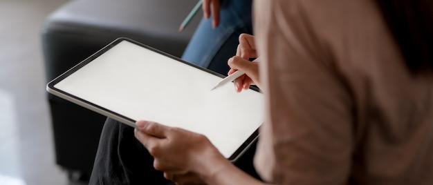 Frau, die mock-up-tablette mit stift verwendet, während sie auf sofa im wohnzimmer sitzt