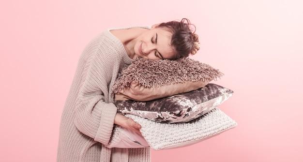 Frau, die moderne drei kissen für sofa, rosa wand im trend, sauberes gemütliches hauptkonzept des minimalismus sauber hält