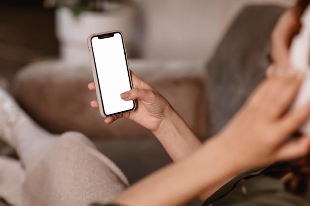 Frau, die modernes smartphone und kopfhörer auf dem sofa zu hause verwendet