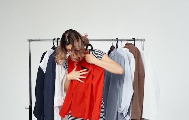Frau, die modische kleidung in einem geschäftseinkaufsarthemd anprobiert.
