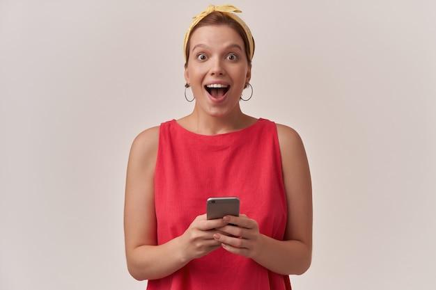 Frau, die modische rote bluse und weißes kopftuch mit natürlichem make-up aufwirft, das wand betrachtet, die sie glückliche überraschte emotion betrachtet, die mit arm halten telefon erstaunt