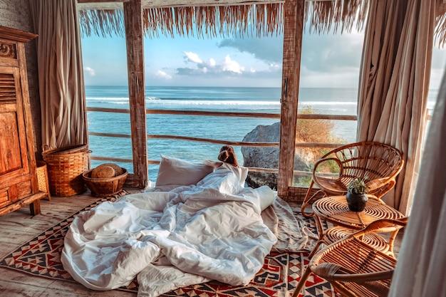 Frau, die morgenferien auf dem tropischen strandbungalow betrachtet meerblick genießt entspannender feiertag uluwatu bali, indonesien