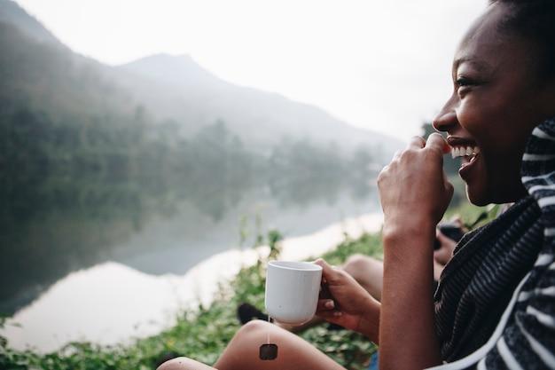 Frau, die morgenkaffee durch einen fluss genießt