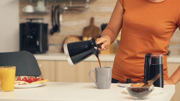 Frau, die morgens aus dem topf heißen kaffee in die tasse gießt. hausfrau zu hause, die frisch gemahlenen kaffee in der küche zum frühstück zubereiten, trinken, kaffee-espresso mahlen, bevor sie zur arbeit geht