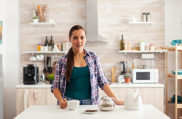 Frau, die morgens eine tasse tee in der küche hält, während sie das frühstück genießt