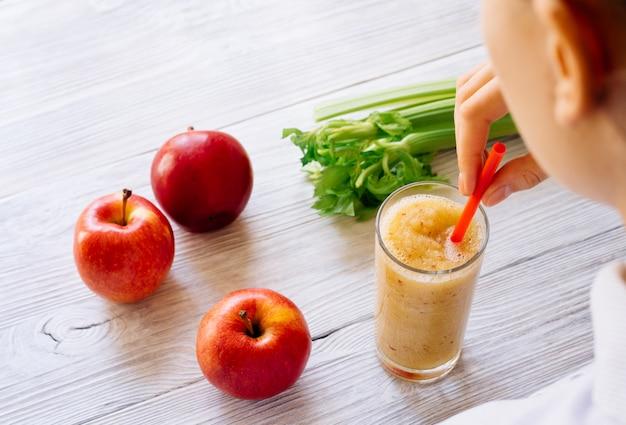 Frau, die morgens einen smoothie von äpfeln und sellerie, ansicht von oben trinkt