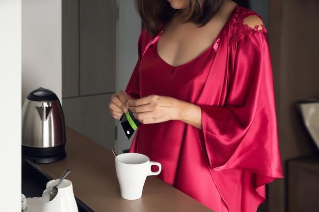 Frau, die morgentee macht, um mit frühstück zu hause zu haben, ein mädchen in einem satin-nachthemd und einem roten gewand, das tee in der küche macht