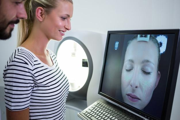 Frau, die mri scan-bericht auf computerbildschirm sucht