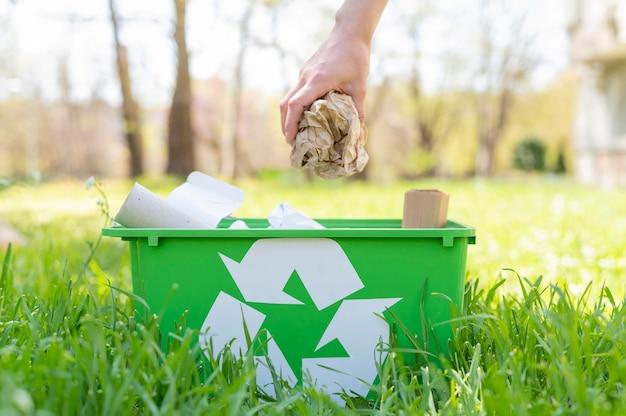 Frau, die müll in recyclingkorb legt