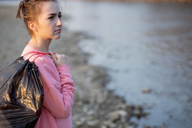 Frau, die müll und plastik aufnimmt, das den strand mit einem müllsack reinigt. freiwilliger umweltaktivist gegen den klimawandel und die verschmutzung der flüsse.