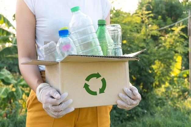 Frau, die müllplastikflaschen in eine box für recyclingkonzept aufnimmt