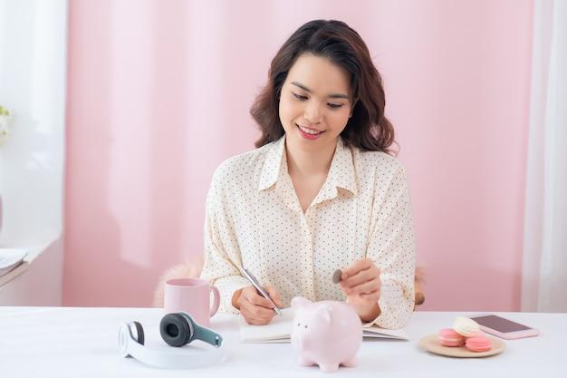Frau, die münze in sparschwein setzt. geld sparen, budget, investition, finanzkonzept