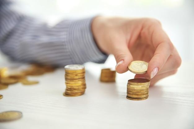 Frau, die münzen auf tisch, nahaufnahme stapelt. sparkonzept