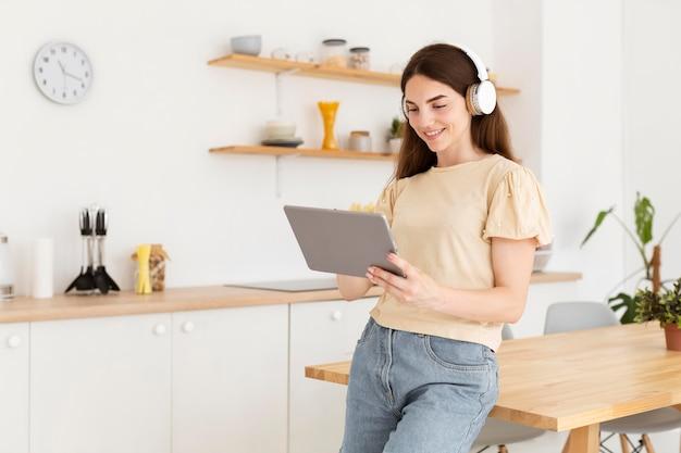 Frau, die musik auf ihren kopfhörer von einem tablett setzt