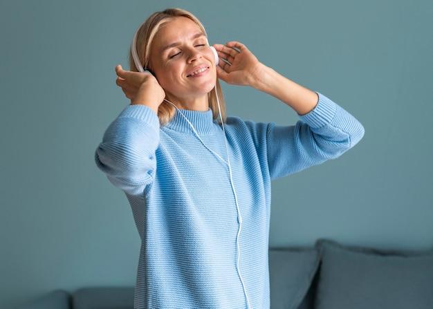 Frau, die musik auf ihren kopfhörern zu hause während der pandemie genießt