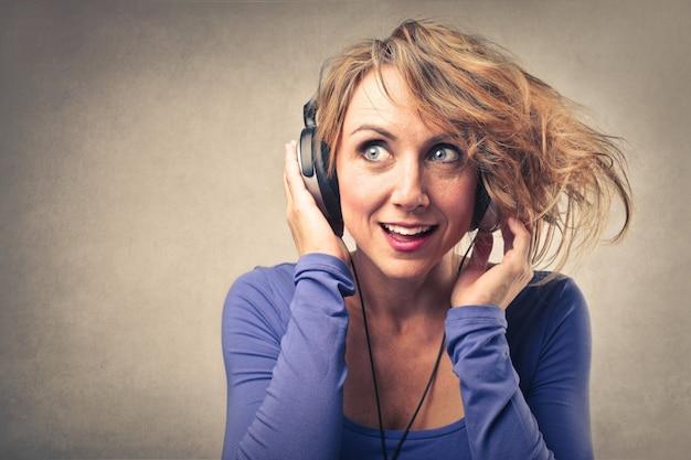 Frau, die musik auf kopfhörern hört