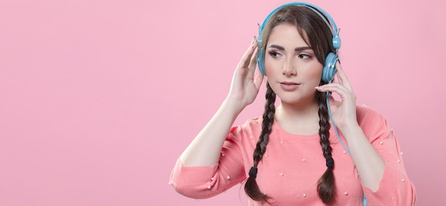 Frau, die musik auf kopfhörern mit kopienraum hört