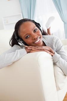 Frau, die Musik auf Sofa genießt