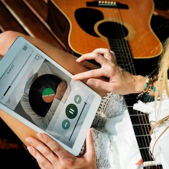 Frau, die musik auf tablette spielt