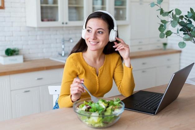 Frau, die musik beim essen des salats hört