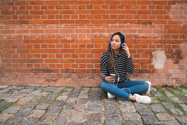 Frau, die musik hört und smartphone verwendet