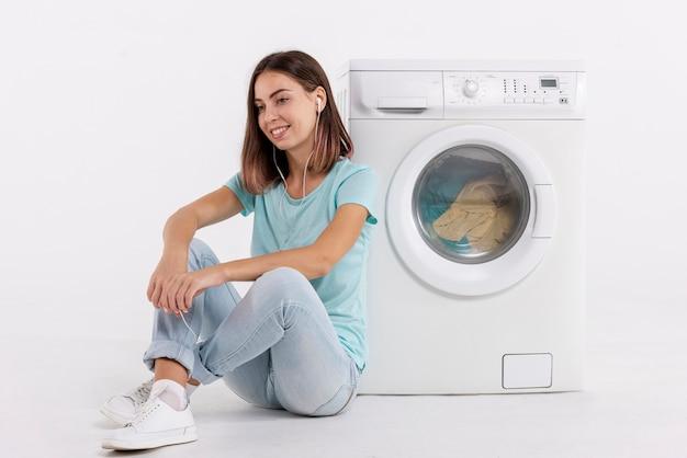 Frau, die musik hört und wäscherei tut